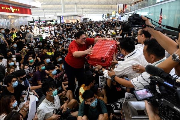 반정부 시위대가 시위를 벌이고 있는 홍콩 국제공항에서 13일(현지 시각) 출국장 안으로 들어가려는 한 관광객이 공항 직원에게 여행용 가방을 부탁하고 있다./AFP