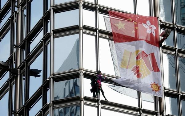 등반가 알랭 로베르가 16일 홍콩 청쿵 센터에 올라 걸개를 걸고 있다. /로이터