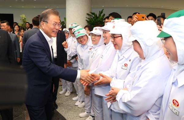 문재인 대통령이 20일 전북 익산 하림 공장에서 직원들과 인사를 나누고 있다./뉴시스