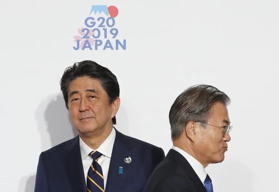 문재인 대통령이 6월 28일 일본 오사카에서 열린 G20(주요 20국) 정상회의에서 기념 촬영 전 아베 신조(왼쪽) 일본 총리를 지나가고 있다. /블룸버그