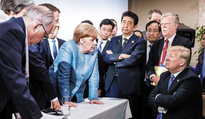 지난해 6월 캐나다 퀘벡에서 열린 G7 정상회의에서 찍힌 이 사진은 미국이 촉발한 자유민주 진영의 분열상을 상징적으로 드러냈다는 평가를 받았다. 탁자를 짚은 앙겔라 메르켈 독일 총리가 팔짱을 낀 채 버티고 앉아 있는 도널드 트럼프 미국 대통령을 응시하고 있다.