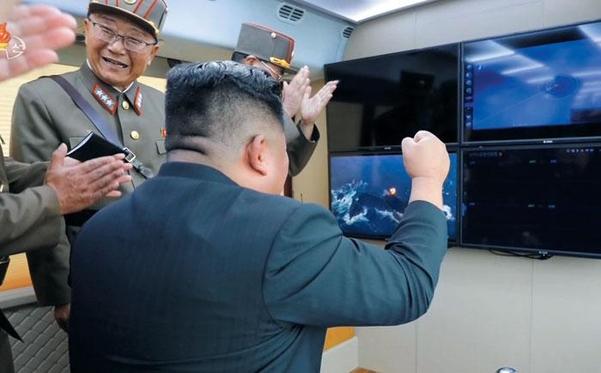 김정은 북한 국무위원장이 지난 16일 단거리 발사체(에이태킴스 미사일 추정) 시험 사격이 성공했다며 주먹을 쥐며 기뻐하는 장면을 조선중앙TV가 17일 공개했다. 왼쪽은 김정은이 '새로운 무기 체계' 개발 공로를 인정해 지난 13일 상장(우리의 중장, 별 3개)으로 진급시킨 북한 국방과학원 소속 전일호. /조선중앙TV