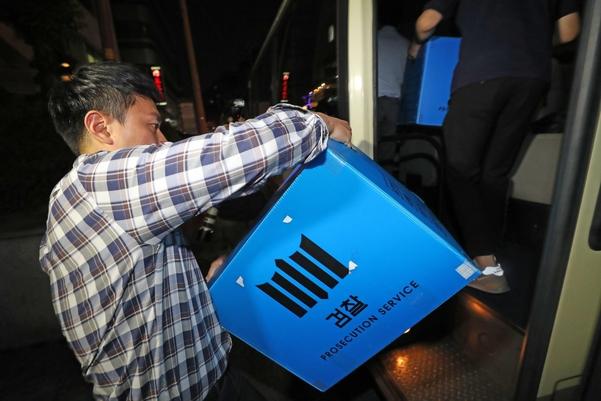 27일 저녁 서울 강남구의 한 빌딩에서 검찰 관계자들이 조국 법무장관 후보자 가족이 투자한 사모펀드 운용사 코링크프라이빗에쿼티 사무실을 압수수색을 마친 뒤 압수품들을 차량으로 옮기고 있다./연합뉴스