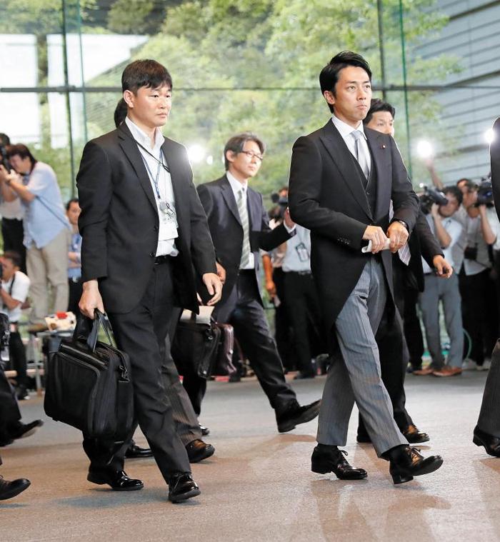 고이즈미 신지로(오른쪽) 신임 일본 환경상이 일본 왕궁에서 열리는 임명식에 참석하기 위해 11일 총리 공관을 떠나고 있다. 올해 38세인 고이즈미는 아베 신조 총리의 정치적 스승인 고이즈미 준이치로 전 총리의 둘째 아들이다.