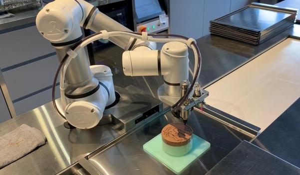 카페봇의 디저트봇이 케이크에 이모지를 그리고 있다./김은영 기자