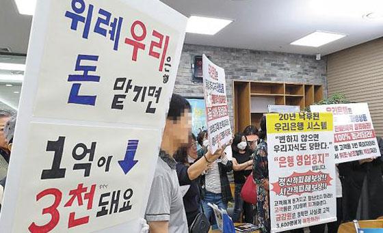 독일 국채금리 연계형 파생결합증권(DLS)에 투자했다가 거액을 날린 투자자들이 19일 오전 경기 성남시 수정구 우리은행 위례신도시지점에 몰려들어 항의 시위를 벌이고 있다.