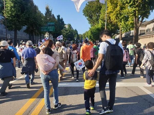 3일 서울 광화문 일대에서 열린 조국 법무부 장관 사퇴를 요구하는 보수 단체 집회에 참석하기 위해 울산에서 상경한 오모(37)씨 가족이 청와대 방면으로 행진하고 있다./ 최지희 기자
