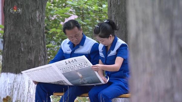 북한 노동당 기관지 노동신문에 실린 시험발사 기사를 읽고 있는 북한 주민의 모습. /연합뉴스