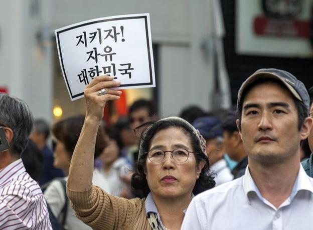 조국 법무부 장관 퇴진을 요구하는 집회가 열린 10월 3일 오후 서울 광화문 동화면세점 빌딩 앞에서 한 시민이 자유 대한민국을 지키자는 구호가 담긴 종이를 들고 있다. /조인원 기자