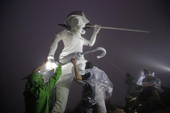 13일 새벽 홍콩의 랜드마크인 사자산(Lion Rock) 정상에서 반(反)정부 시위자들이 '자유의 여인상'을 설치하고 있다. /연합뉴스