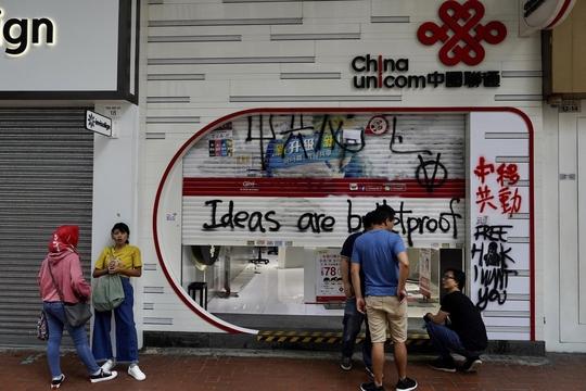 지난 7일 홍콩 도심에 위치한 중국 이동통신사 '차이나유니콤'이 시위대의 공격을 받았다. 점포 밖에서 한 직원이 청소하고 있다. /연합뉴스