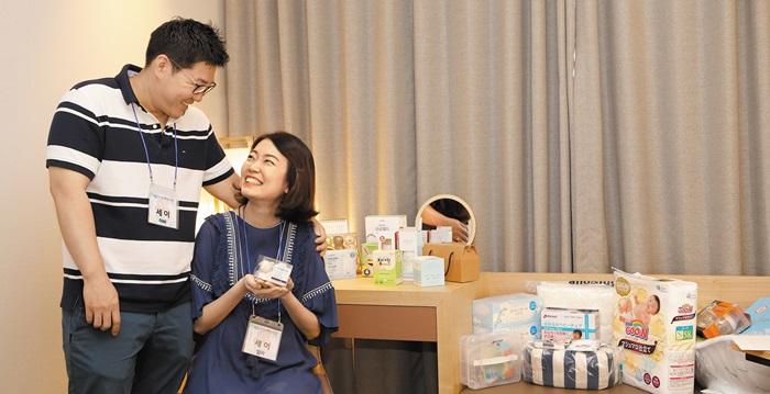 지난 6월 매일유업이 개최한 만월여행에 참석한 한 예비 부모가 호텔 객실에 마련된 임신 축하 선물을 보며 즐거워하고 있다.