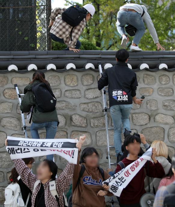 한국대학생진보연합이 18일 오후 서울 중구 주한 미국대사관저에서 방위비분담금 협상 관련 기습 농성을 하기 위해 담벼락을 넘고 있다. /뉴시스