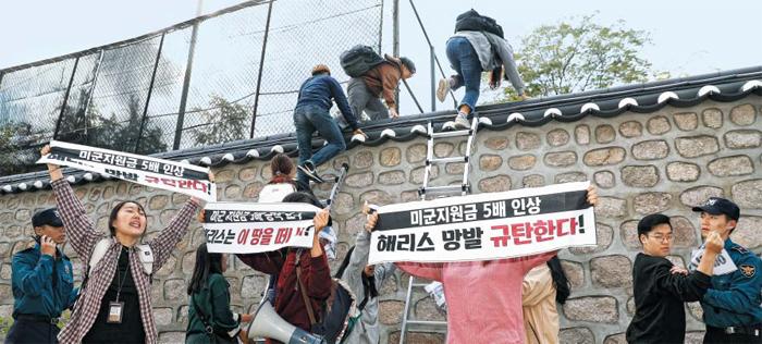 18일 오후 3시쯤 친북 단체인 한국대학생진보연합(대진연) 회원들이 서울 중구 정동 주한 미국대사관저 담장에 사다리를 대고 관저 안으로 넘어들어가고 있다. 현장에 있던 경찰은 대진연 회원에게 붙들려 저지당하거나(오른쪽 끝) 무전으로 지원 요청하느라(왼쪽 끝) 이들의 월담을 제지하지 못했다. 관저에 기습 침입한 이들은 관저 현관까지 올라가 반미 플래카드를 펼치고 구호를 외쳤다.