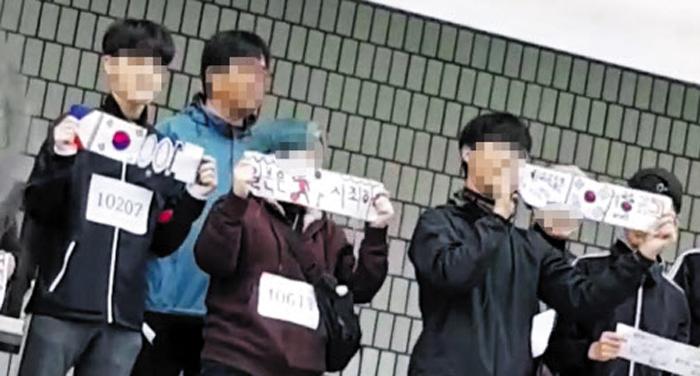 지난 17일 서울 A고의 '달리기 걷기 어울림 한마당' 행사에서 단상에 오른 학생들이 '일본은 사죄하라'는 구호를 적은 종이와 태극기를 펼쳐보이고 있다. A고 일부 교사는 행사 1주일 전부터 학생들에게 이 같은 그림을 만들도록 했다.