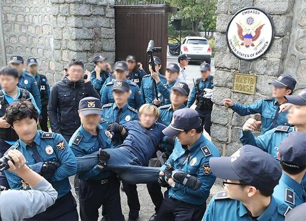 지난 18일 오후 서울 중구 정동에 위치한 주한미대사관저 담장을 넘은 한국대학생진보연합 학생들을 경찰이 연행하고 있다. /뉴시스