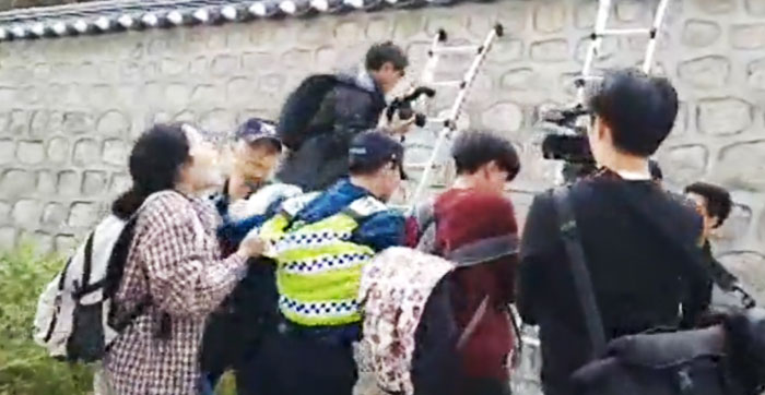 지난 18일 서울 중구 주한 미국 대사관저로 담을 넘어 침입하려던 한국대학생진보연합의 여성 회원(맨 왼쪽)이 이들을 저지하려는 경찰을 뒤에서 잡아당기고 있다.