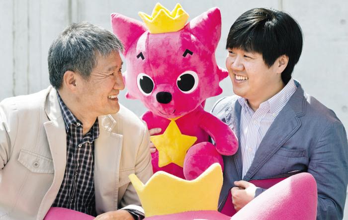 핑크퐁 캐릭터를 가운데 두고 마주 앉은 스마트스터디의 김민석(오른쪽) 대표와 아버지 김진용(왼쪽) 삼성출판사 대표.