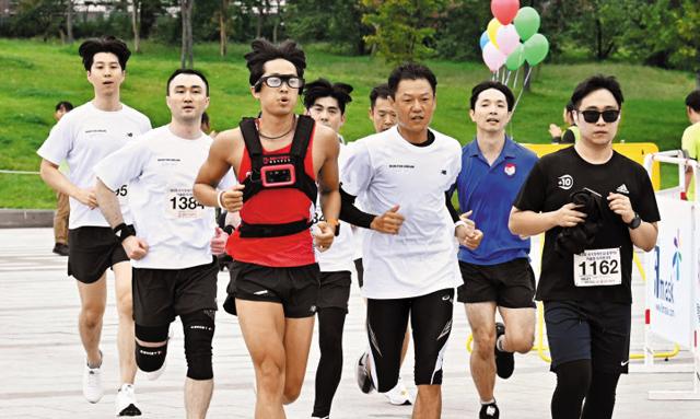 시각장애인 마라토너 한동호씨가 시각장애인용 웨어러블 스마트기기 '웰컴드림글래스'를 착용하고 일반인들과 함께 마라톤 코스를 뛰고 있다.