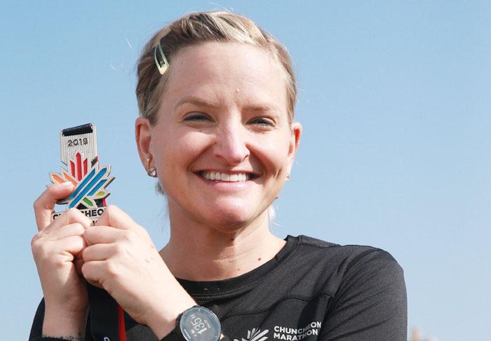 미국 러닝 브랜드 '브룩스'의 수석 디자이너 캘리 도슨씨가 27일 춘천마라톤 하프 코스를 달린 뒤 완주자에게 주는 메달을 들고 미소 짓고 있다.