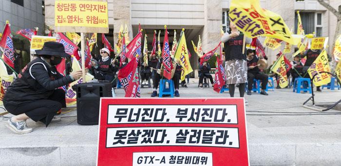 지난 22일 서울 강남구 청담동 도로변에서 청담동 주택가 지하로 수도권광역급행철도(GTX)-A 노선이 통과하는 걸 반대하는 주민들이 '주택붕괴' '열차탈선' 등이 쓰인 깃발을 들고 시위를 벌이고 있다.