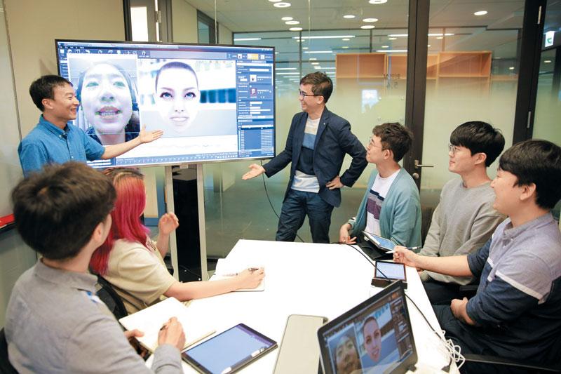 엔씨소프트 소속 인공지능(AI) 분야 연구원들이 회의실 안에 있는 화면을 보면서 음성에 맞춰 게임 캐릭터의 표정을 자동으로 생성하는 기술(보이스 투 애니메이션)에 대해 의견을 나누는 모습.