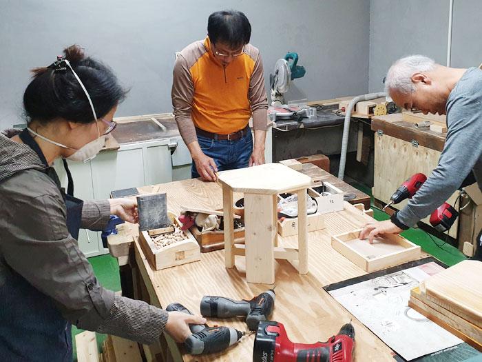 지난달 25일 서울 성북구의 한 아파트단지 공방에서 주민들이 폐가구를 수리해 의자와 수납상자 등을 만들고 있다.