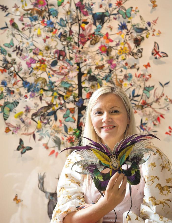 """나무 위에 나비가 가득 내려앉은 콜라주 작품 앞에 앉은 크리스트자나 윌리엄스. 그는 """"사람들이 내 작품을 보며 잠시 도심 속 일상을 벗어나 동화 속 환상의 세계로 떠난 듯한 기분을 얻길 원한다""""고 했다."""