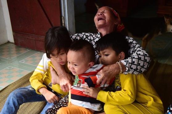 영국으로 밀입국하려다 희생된 한 남성의 어머니가 베트남에서 손주들을 껴안고 오열하고 있다 /EPA 연합뉴스