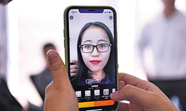 한 여성이 알리바바의 온라인쇼핑몰 앱(모바일 응용프로그램)의 'AR(증강현실) 메이크업' 기능을 사용해 립스틱을 고르고 있다.