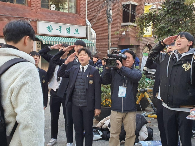 14일 서울 서초고 앞에서 중동고 응원단 학생들이 수능시험을 보는 선배 수험생에게 거수 경례를 하고 있다./ 정민하 기자