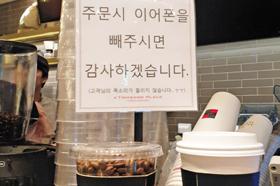 """13일 서울 강남구 한 카페에 """"주문 시 이어폰을 빼주시면 감사하겠습니다""""라는 문구가 붙어 있다."""