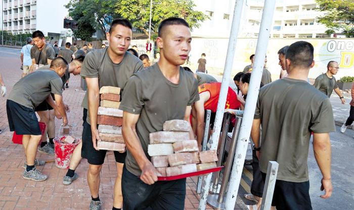 홍콩에 주둔하는 중국 인민해방군 군인들이 16일 카우룽통 지역에서 시위대가 던져놓은 벽돌을 치우고 있다. 이날 시위로 어지럽혀진 거리 청소에 나선 군인 중에는 '특전8중대' '쉐펑(雪楓) 특전대대'라고 쓰인 운동복을 입은 사람도 있었다.