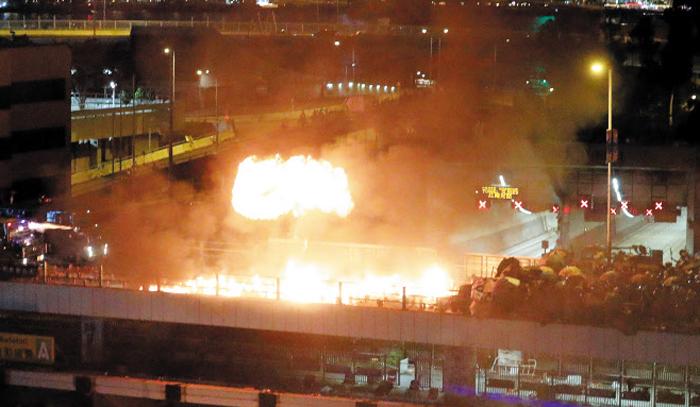 17일 저녁 홍콩 시위대와 홍콩 경찰 장갑차가 크로스하버 터널 인근 육교에서 대치하는 가운데 시위대가 육교에 쌓아놓은 화염병에 불이 붙어 불길이 치솟고 있다. 이날 시위대가 화염병을 던져 경찰 장갑차가 불타기도 했다. 시위대는 14일부터 카우룽반도와 홍콩섬을 연결하는 크로스하버 터널을 막고 있다.