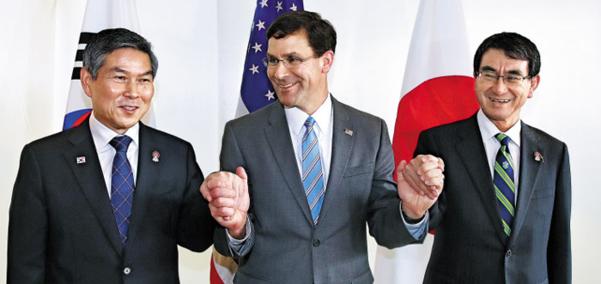 """마크 에스퍼(가운데) 미국 국방장관이 17일 방콕 아바니 리버사이드 호텔에서 열린 한·미·일 국방장관 회담에서 정경두(왼쪽) 국방장관과 고노 다로 일본 방위상의 손을 맞잡고 있다. 처음엔 굳은 표정으로 서 있던 정 장관과 고노 방위상은 에스퍼 장관이 """"동맹, 동맹 맞죠?(allies, allies, right?)""""라고 묻자 뒤늦게 웃음을 보였다. /연합뉴스"""