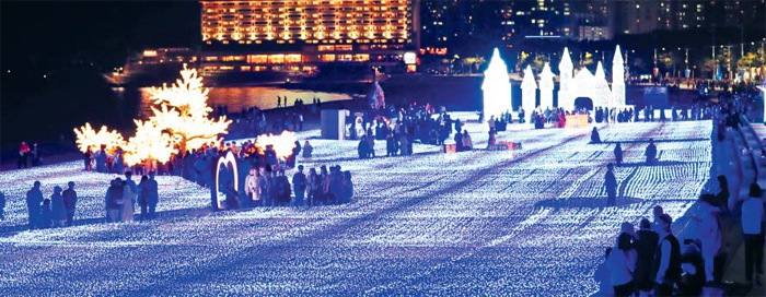 '제6회 해운대 빛 축제'가 열리고 있는 부산 해운대해수욕장을 찾은 사람들이 바다를 배경으로 다채로운 조명이 빛나고 있는 행사장을 걷고 있다. 축제는 내년 1월 27일까지 열린다.