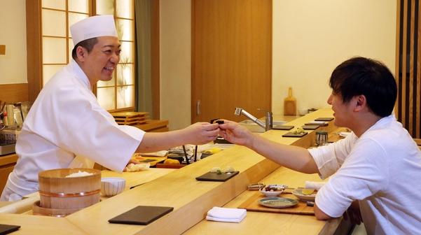 서울 청담동 '스시 코우지'를 운영하는 일본인 요리사 코우지 나카무라씨가 스시를 만들어 손님에게 내주고 있다. 이 같은 식당 특유의 분위기가 맛을 배가시킨다고 전문가들은 말한다. /이진한 기자