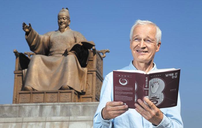 독일인 알브레히트 후베 교수가 서울 광화문광장 세종대왕 동상 앞에서 자신의 책을 펼쳐 들었다.