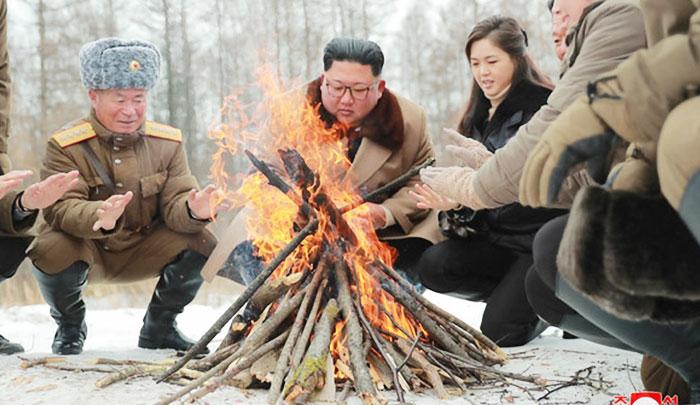김정은(가운데) 북한 국무위원장과 부인 리설주(오른쪽)가 백두산에 올라 북한군 주요 간부들과 함께 모닥불을 쬐고 있다.