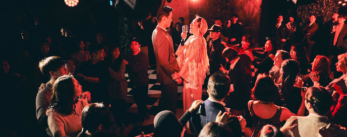 21일 서울 중구 그레뱅 뮤지엄에서 개막한 이머시브 공연 '위대한 개츠비' 중 한 장면. 배우들이 노래를 부르고, 관객들끼리 어깨에 손을 올리고 이들 주위를 도는 '기차 놀이'를 하고 있다.