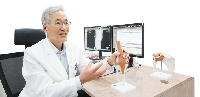 용인분당 예스병원의 김인권 병원장이 환자에게 인공 관절 수술에 대해 설명하고 있다.