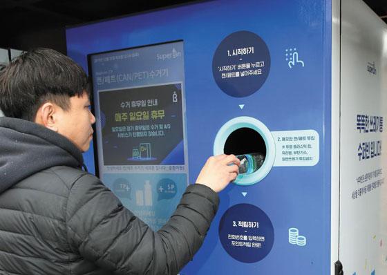 지난 26일 서울 여의도공원에서 한 시민이 소셜스타트업 수퍼빈의 재활용 분리수거기에 페트병을 넣고 있다.