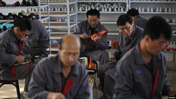 지난 2012년 중국 랴오닝성 단둥의 한 마을에서 북한 노동자들이 신발을 만들고 있다./로이터·VOA