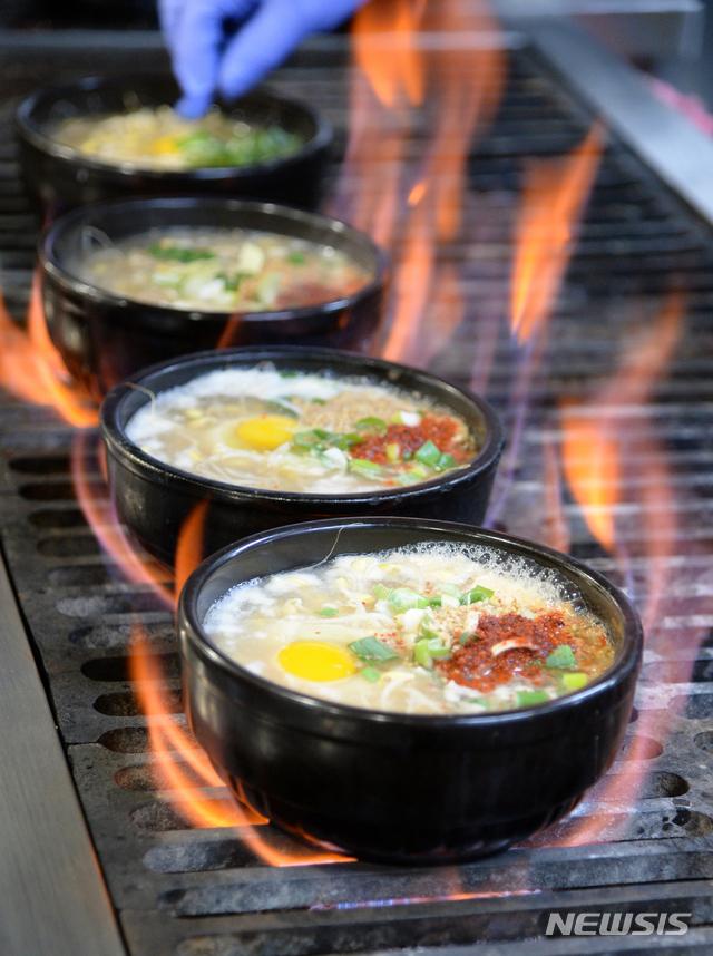 19일 전북 전주시 삼백집 전주본점에 대표 음식 '끓이는 방식(직화)'의 콩나물 국밥이 맛있게 익어가고 있다.