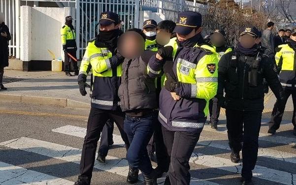 14일 서울 종로구 정부서울청사 앞에서 천막 철거를 막고 자해를 시도한 탈북민 이모(46)씨가 경찰에 연행되고 있다. /독자 제공