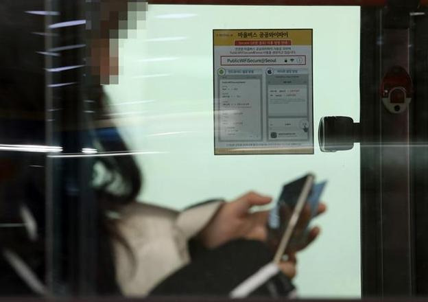 서울시가 마을버스 전 노선에 무료 공공 와이파이를 구축했다고 밝힌 작년 11월 20일 서울 홍제역 인근 정류장에 대기 중인 한 마을버스에 관련 안내문이 붙어 있다. /연합뉴스