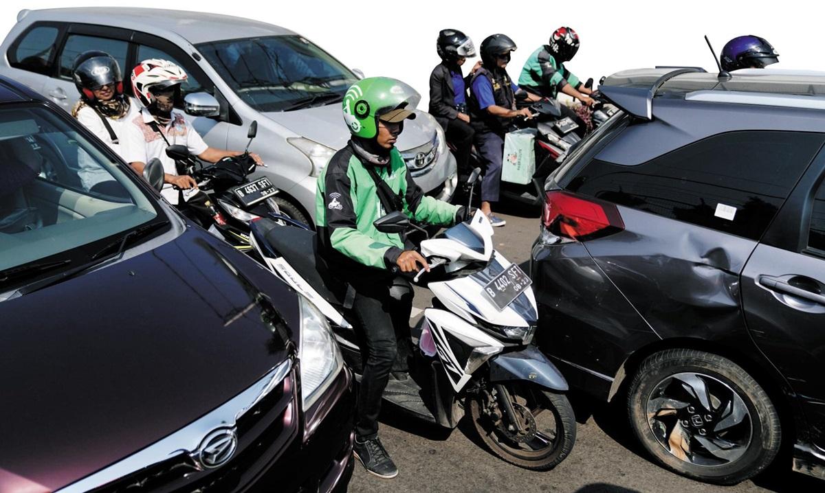인도네시아 수도 자카르타 시내에서 녹색 상의를 입은 고젝 배달원들이 오토바이를 타고 자동차 사이를 가로지르며 고객의 물건을 운송하고 있다.