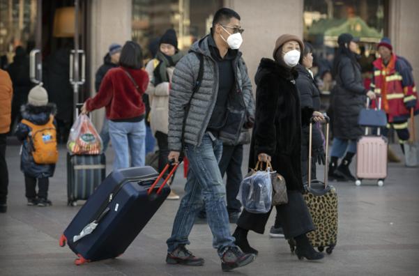 20일 베이징 기차역 앞에서 여행객들이 마스크를 쓴 채 걸어가고 있다. 중국 최대 명절인 춘제를 앞두고 수억명의 대이동이 시작돼 '우한 폐렴' 확산 우려가 커지고 있다. /연합뉴스