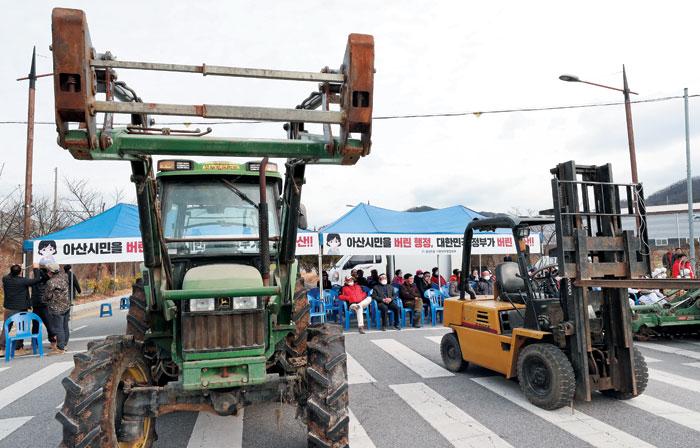 29일 오후 충남 아산시 초사동 경찰인재개발원 정문 앞에서 아산 지역 주민들이 왕복 4차선 도로를 농기계들로 가로막고 항의 시위를 하고 있다.