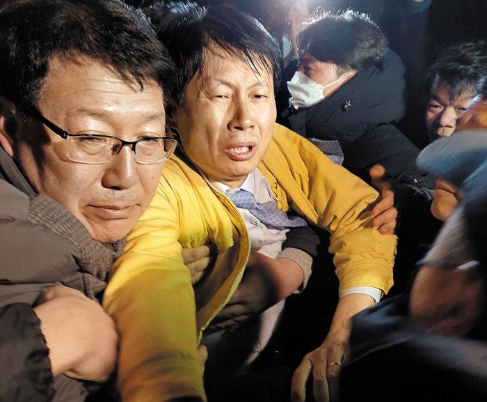 김강립(왼쪽 둘째) 보건복지부 차관이 29일 오후 10시 30분쯤 충북 진천 국가공무원 인재개발원 정문 앞에서 주민들의 거센 항의가 이어지자 경찰의 호위를 받으며 현장을 빠져나가고 있다.
